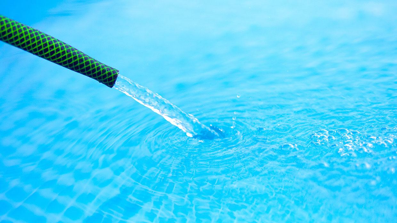 Swimmingpool wird mit Gartenschlauch befüllt