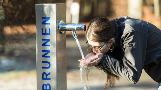 Frau trinkt aus Trinkbrunnen